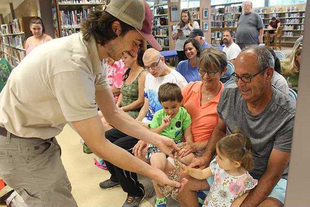 kid touches snake web
