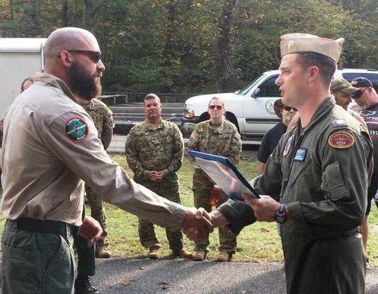 Jon Ellis Receiving letter of commendation from commander Jason Gustin