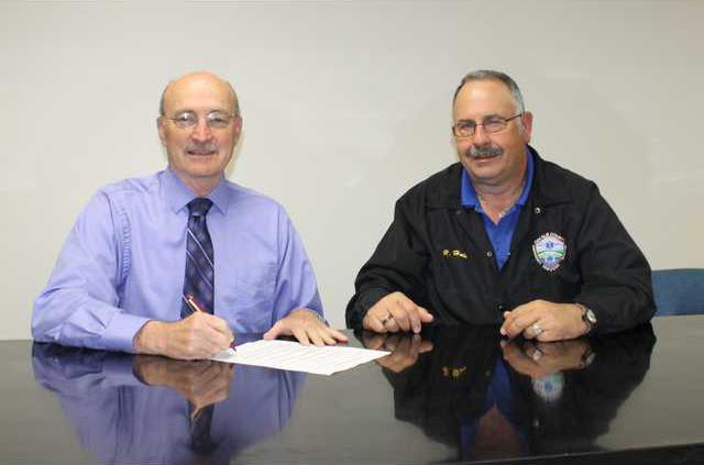 Mayor Tim Striblimg signs a proclamation designating----- EMS week in DeKalb County while EMS Director Hoyte Hale looks on.